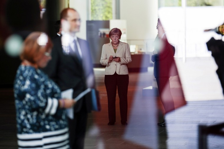 "German Chancellor Angela Merkel uses her mobile phone as she prepares to welcome participants at the ""West Balkan Conference"" at the chancellery in Berlin August 28, 2014. (Markus Schreiber/Reuters)"