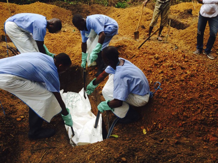Volunteers lower a corpse, which is prepared with safe burial practices to ensure it does not pose a health risk to others and stop the chain of person-to-person transmission of Ebola, into a grave in Kailahun August 2, 2014. Hundreds of troops were deployed in Sierra Leone and Liberia on Monday to quarantine communities hit by the deadly Ebola virus, as the death toll from the worst-ever outbreak reached 887 and three new cases were reported in Nigeria. Picture taken August 2, 2014. (REUTERS/WHO/Tarik Jasarevic/Handout via Reuters)