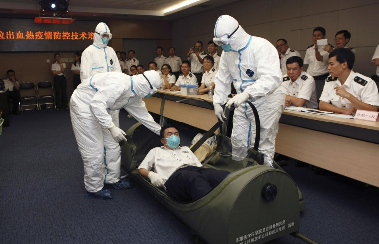 Health inspection officers help a mock patient (C) get into a negative pressure isolation stretcher, during a drill to demonstrate the procedures of transporting an Ebola victim, at Shenzhen Entry-exit Inspection and Quarantine Bureau, in Shenzhen, Guangdong province August 14, 2014. China's quarantine authority has intensified inspections at customs to prevent the deadly Ebola virus, which killed over 1,000 people in Africa, from entering the country, Xinhua News Agency reported. Picture taken August 14, 2014. (REUTERS/Stringer)