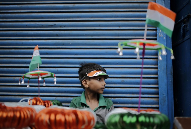 A boy waits for customers as he sells paper flags and other decorative items painted in the colours of the Indian national flag on the eve of India's Independence Day celebrations in the old quarters of Delhi August 14, 2014. India commemorates its Independence Day on Friday. (Anindito Mukherjee/Reuters)