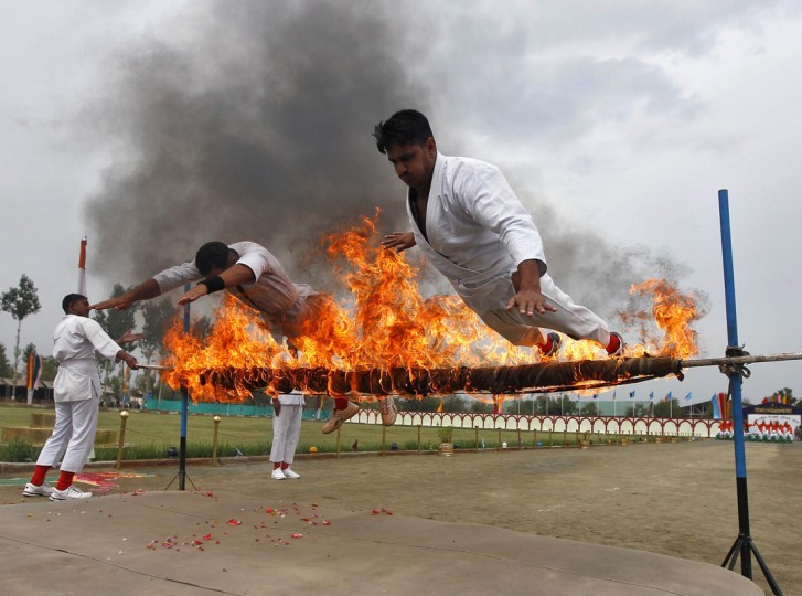 India's Central Reserve Police Force (CRPF) personnel perform a stunt during the passing out parade in Humhama, on the outskirts of Srinagar August 28, 2014. According to authorities from CRPF, 368 new policemen were formally inducted into the force after completing a 44-week rigorous training course and will be deployed in different parts of India. (Danish Ismail/Reuters)