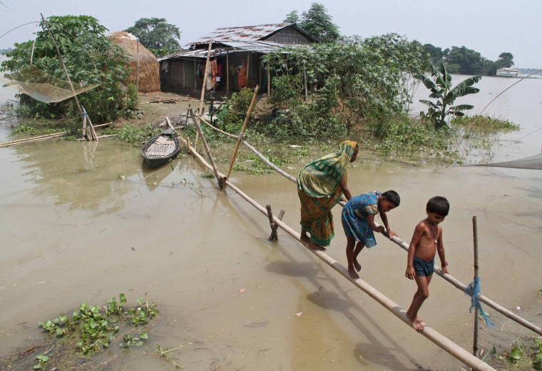 Villagers use a makeshift bamboo bridge to move across flooded areas of Morigaon district in the northeastern Indian state of Assam . The latest heavy rains have caused landslides and floods in many parts of India and Nepal, where at least 90 people have been killed since Thursday. (Reuters)