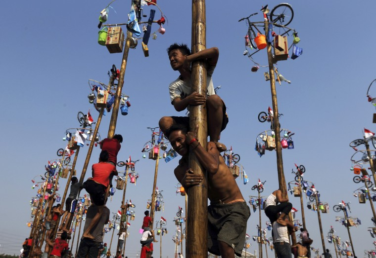 """Participants react as they hold on to a greased pole during the """"Panjat Pinang"""" event organised in celebration of Indonesia's 69th Independence Day at Ancol Dreamland Park in Jakarta August 17, 2014. The annual event sees participants working together to reach the top of slippery poles where prizes are hung. (Beawiharta/Reuters)"""