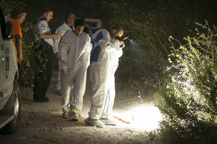A forensic team member takes a picture near the place where a body was found next to Ein Karem village, near Jerusalem, August 28, 2014. Israeli police and volunteers found a body near a forest in Jerusalem on Thursday while searching for Aaron Sofer, a 23-year-old American student who went missing last week, but said no formal identification had yet been made. Sofer, a Jewish seminary student from New Jersey, vanished on August 22, 2014 while walking in woods not far from Israel's Yad Vashem Holocaust museum, Israeli police spokesman Micky Rosenfeld said. (Baz Ratner/Reuters)