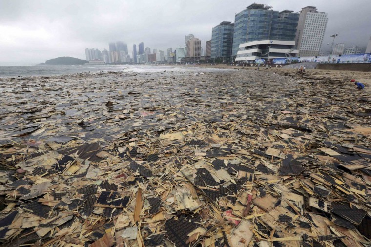 Pieces of wood and debris believed by the Busan Coast Guard to be from a cargo ship which sank in the sea off Busan a year ago, cover Haeundae Beach after Typhoon Nakri battered Busan August 4, 2014. (Jo Jung-ho/Yonhap/Reuters)
