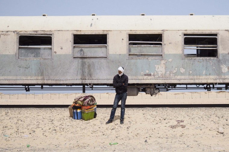A passenger on a SNIM train carrying iron ore and mine workers waits for transport after arriving in Nouadhibou June 25, 2014. (Joe Penney/Reuters)