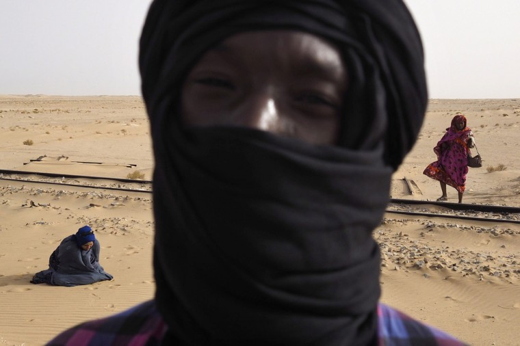 Passengers take a break to pray while travelling on SNIM train carrying iron ore and mine workers across the desert outside Nouadhibou June 25, 2014. (Joe Penney/Reuters)