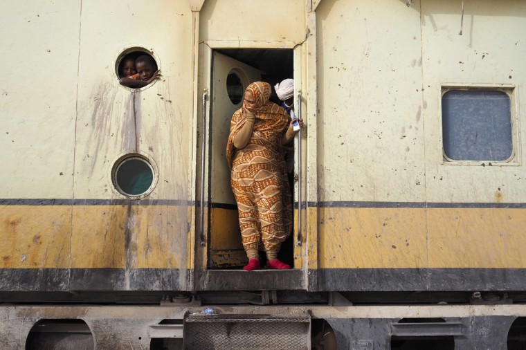Passengers take a break while travelling on a SNIM train carrying iron ore and mine workers across the desert outside Nouadhibou June 25, 2014. (Joe Penney/Reuters)