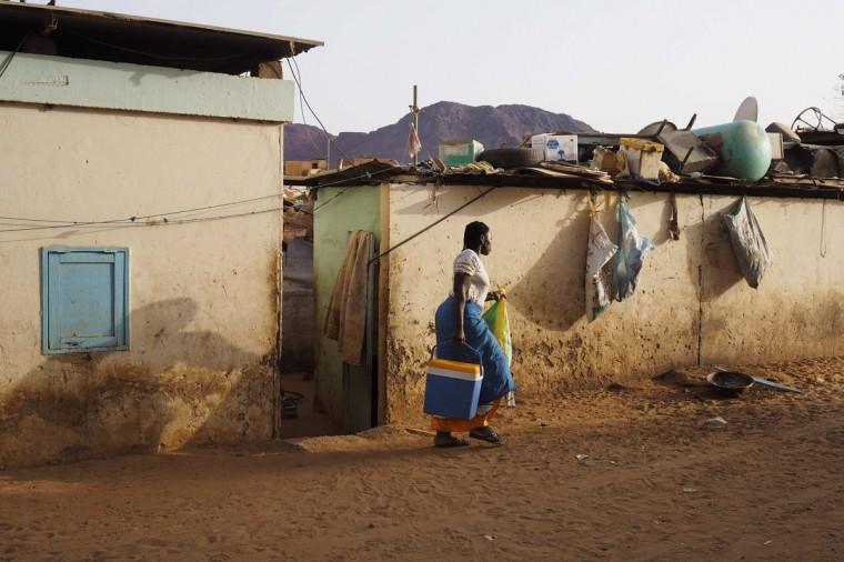 A woman walks in front of houses for SNIM workers in the iron ore mining town of Zouerate June 23, 2014. (Joe Penney/Reuters)