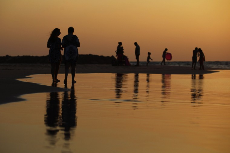 Israeli beach-goers are seen on the shore of the Mediterranean sea at the southern Israeli city of Ashkelon. An open-ended ceasefire in the Gaza war held on Wednesday as Prime Minister Benjamin Netanyahu faced strong criticism in Israel over a costly conflict with Palestinian militants in which no clear victor emerged. (Amir Cohen/Reuters)