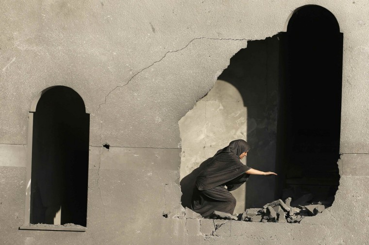 A Palestinian woman inspects her house that witnesses said was damaged during an Israeli airstrike in Gaza City. Hamas militants in the Gaza Strip fired rockets at Israel for a second day on Wednesday after fighting resumed with the collapse of truce talks and an Israeli air strike that killed three people in Gaza. (Suhaib Salem/Reuters)