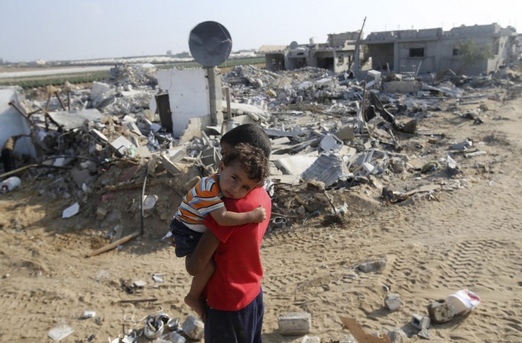 A Palestinian boy carries his brother next to the remains of their house, which witnesses said was destroyed in the Israeli offensive, during a 72-hour truce in Khan Younis the southern Gaza Strip . The threat of renewed war in Gaza loomed on Wednesday as the clock ticked toward the end of a three-day ceasefire without a sign of a breakthrough in indirect talks in Cairo between Israel and the Palestinians. Israeli negotiators returned to Egypt after overnighting in Israel, with the truce in the month-old hostilities that have killed 1,945 Palestinians in the Gaza Strip and 67 on the Israeli side due to expire at 2100 GMT (5 p.m. EDT). (Ibraheem Abu Mustafa/Reuters)