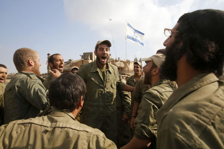 Israeli soldiers from the armoured corps celebrate after returning to Israel from Gaza August 5, 2014. Israel pulled its ground forces out of the Gaza Strip on Tuesday and started a 72-hour ceasefire with Hamas mediated by Egypt as a first step towards negotiations on a more enduring end to the month-old war. (REUTERS/Baz Ratner)