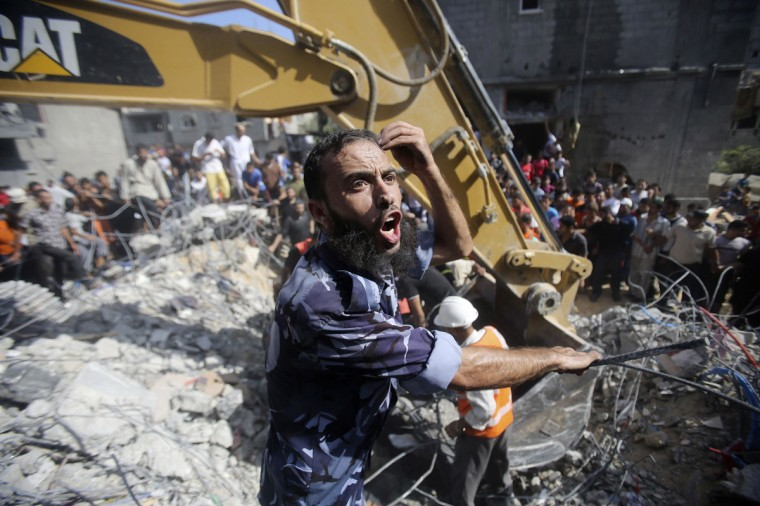 A Palestinian policeman reacts as rescue workers search for victims under the rubble of a house, which witnesses said was destroyed in an Israeli air strike that killed three senior Hamas military commanders, in Rafah in the southern Gaza Strip August 21, 2014. An Israeli air strike killed three senior Hamas military commanders in the Gaza Strip on Thursday, the Islamist group said, the clearest sign yet Israel is focusing its assault on those leading attacks from the Palestinian enclave. The Israeli military had no immediate comment on what would constitute the killing of the most senior Hamas men since it launched its offensive on Gaza six week ago with the declared aim of curbing rocket fire into its territory. (Ibraheem Abu Mustafa/Reuters)