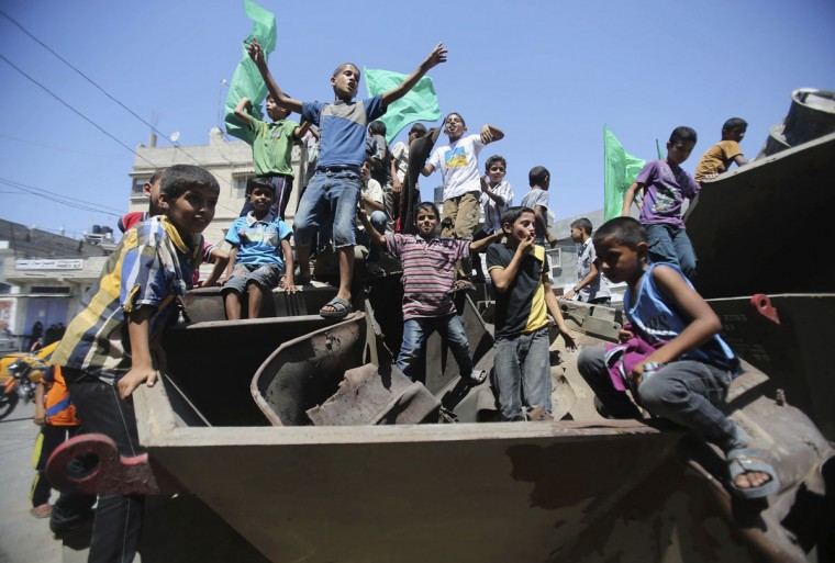 Palestinian children waving Hamas flags cheer as they stand on Israeli military equipment, which witnesses said was left behind by Israeli forces during a ground offensive, in Khan Younis in the southern Gaza Strip August 5, 2014. Israel pulled its ground forces out of the Gaza Strip on Tuesday and began a 72-hour truce with Hamas mediated by Egypt as a first step towards negotiations on a more enduring end to the month-old war. Gaza officials say the war has killed 1,834 Palestinians, most of them civilians. Israel says 64 of its soldiers and three civilians have been killed since fighting began on July 8, after a surge in Palestinian rocket launches. (REUTERS/Ibraheem Abu Mustafa)
