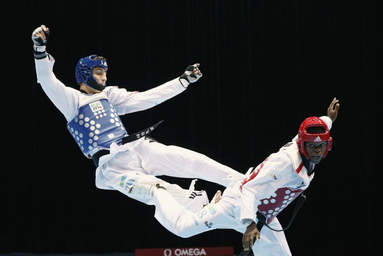 Lebanon's Eric Melki (L) fights against Gabon's Davy Endamne Dzime during their men's -55kg round of 16 taekwondo match at the 2014 Nanjing Youth Olympic Games in Nanjing, Jiangsu province, August 18, 2014. (REUTERS/Aly Song)
