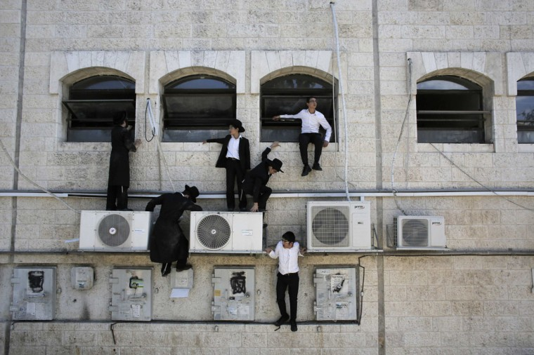 Ultra-Orthodox Jewish boys climb down a wall near the scene of a suspected attack in Jerusalem August 4, 2014. A Palestinian killed an Israeli and overturned a bus with a construction vehicle on Monday and a gunman wounded a soldier in attacks in Jerusalem that appeared to be a backlash against Israel's Gaza war. There were no passengers on the bus, in an ultra-Orthodox Jewish neighborhood of the city. Surveillance video broadcast on Israeli television showed the yellow excavator's mechanical arm tearing into the side of the bus as it lay on the sidewalk. (Ammar Awad/Reuters)