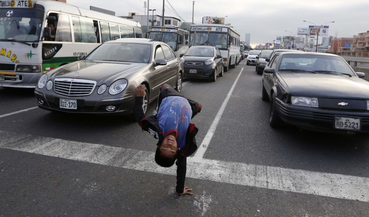 Eleven-year-old Renzo somersaults at a traffic junction in the San Borja district in Lima August 18, 2014. Renzo and his 9-year-old brother Gianpierre perform on streets to make a living from tips given by drivers, make an average of $7 a day between the two brothers. They work on the streets after school to help their parents, whom they live with, with household expenses. (REUTERS/Mariana Bazo)