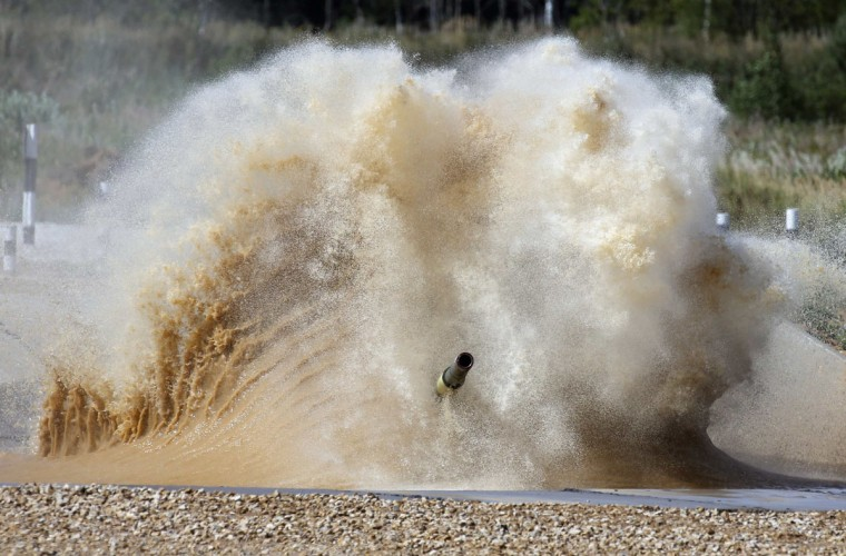 A tank drives through a water obstacle on the course of the Tank Biathlon world championship in Alabino outside Moscow August 4, 2014. The tank competition, where teams compete in tests of driving and shooting, will for the first time bring together crews from 12 countries: Angola, Armenia, Belarus, Venezuela, India, Kazakhstan, Kyrgyzstan, China, Kuwait, Mongolia, Russia and Serbia, local media reported. (Maxim Shemetov/Reuters)