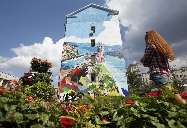A woman walks past a mural on the side of a building which depicts the Swallow's Nest castle overlooking the Black Sea outside the Crimean town of Yalta, in Moscow. (Maxim Zmeyev/Reuters)