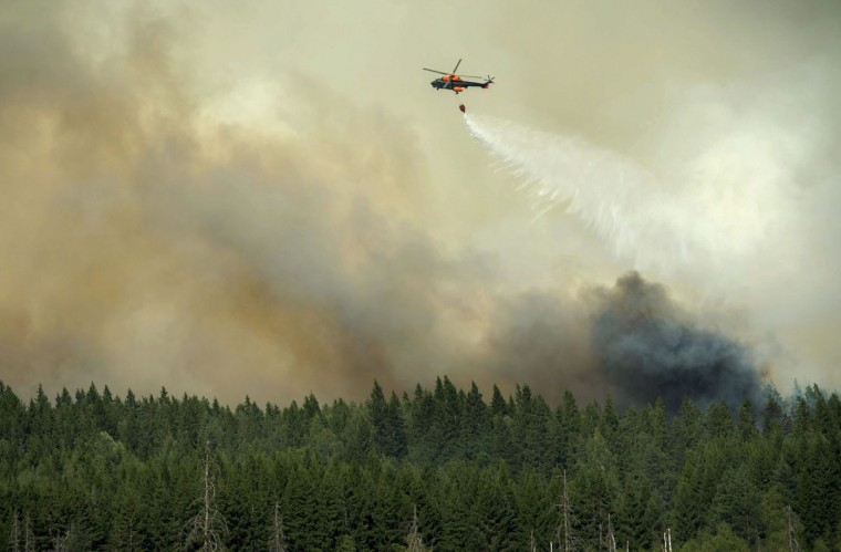 A helicopter dumps its load of water on the wildfire front just outside the evacuated village of Gammelby near Sala, central Sweden August 4, 2014. The fire, covering thousands of hectares, is in its fifth day and firefighters believe it will burn for weeks or even months. It is classified as the worst forest fire in Sweden's modern history. (Fredrik Sanberg/TT News Agency/Reuters)