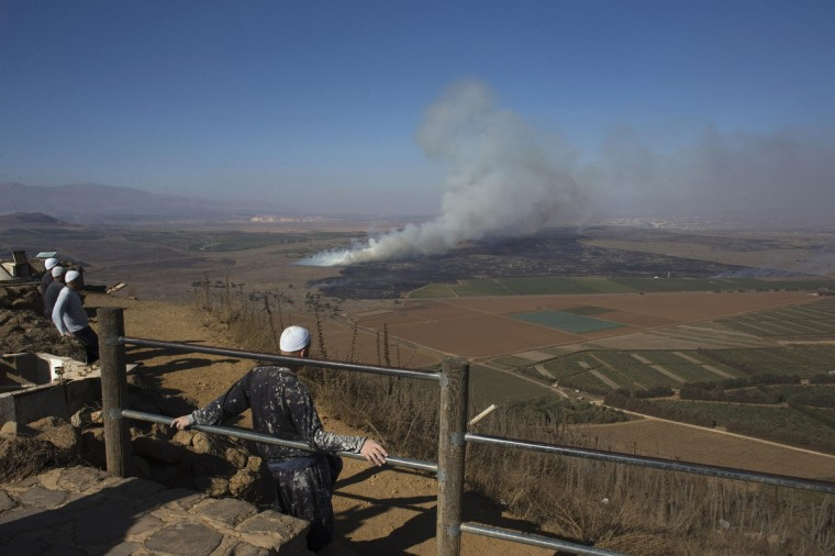 Druze men look at smoke rising on the Israeli-controlled side of the line dividing the Israeli-occupied Golan Heights from Syria following fighting near the Quneitra border crossing. Al Qaeda's Syria wing Nusra Front and other Islamist fighters have taken control of the border crossing, a group monitoring the Syrian conflict said on Wednesday. The fighters captured the Quneitra post on the Syrian side from forces loyal to President Bashar al-Assad after fierce clashes, the Syrian Observatory for Human Rights said. The crossing is monitored by the United Nations, which oversees traffic between the two enemy countries but the distance between the two warring adversaries' posts is some 200 meters (yards). During the fighting, a stray bullet wounded an Israeli soldier in the Golan Heights and Israel responded with artillery fire at two Syrian army positions, the Israeli military said. It was the latest spillover of violence from the three-year conflict. (Ronen Zvulun/Reuters)