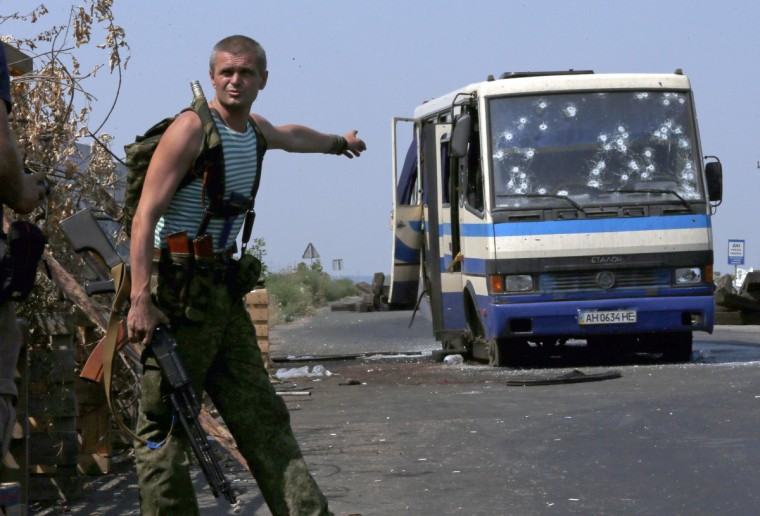 An armed pro-Russian separatist points at a bus riddled with bullet holes at a checkpoint on the outskirts of Donetsk, . Twelve Ukrainian nationalist fighters, battling a pro-Russian insurgency in eastern Ukraine, were killed early on Wednesday and an unknown number taken captive when rebels ambushed their bus, a spokesman for their group said. The separatists opened fire on the bus, that was taking the men to fight just outside the rebel-held city of Donetsk, at the nearby village of Mandrykino, said a spokesman for Right Sector, extreme nationalists who are supporting government forces. (Sergei Karpukhin/Reuters)