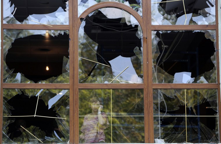 A woman looks out from a damaged window following what locals say was shelling by Ukrainian forces in Donetsk August 7, 2014. The Ukrainian government said on Thursday it was suspending a ceasefire with separatist rebels at the crash site of the Malaysian airliner after an international recovery mission had been halted. (Sergei Karpukhin/Reuters)
