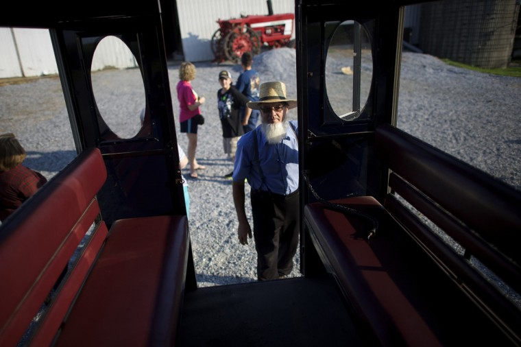 John Fisher, an Amish buggy driver, closes the door of his buggy during a tour through Lancaster County, Pennsylvania August 9, 2014. (Mark Makela/Reuters)