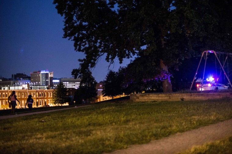 Residents walk through Collington Square Park minutes before a curfew law took effect in Baltimore August 8, 2014. Mayor Stephanie Rawlings-Blake said the measure, which took effect on Friday, was aimed at getting children off the streets before they were put in danger. (James Lawler Duggan/Reuters)