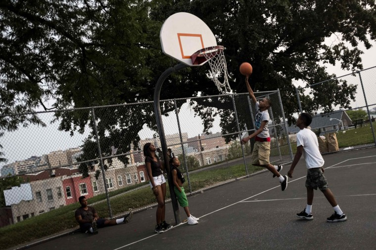 Children play basketball at Collington Square Park less than an hour before a curfew law took effect in Baltimore August 8, 2014. Mayor Stephanie Rawlings-Blake said the measure, which took effect on Friday, was aimed at getting children off the streets before they were put in danger. (James Lawler Duggan/Reuters)