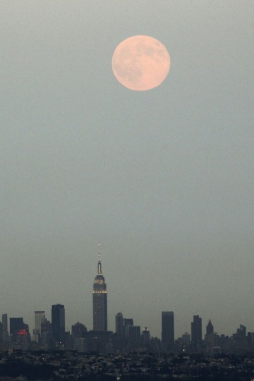 """A full moon known as a """"supermoon"""" rises over the skyline of New York and the Empire State Building as seen from the Eagle Rock Reservation in West Orange, New Jersey, August 10, 2014. The astronomical event occurs when the moon is closest to the Earth in its orbit, making it appear much larger and brighter than usual. (Eduardo Munoz/Reuters)"""