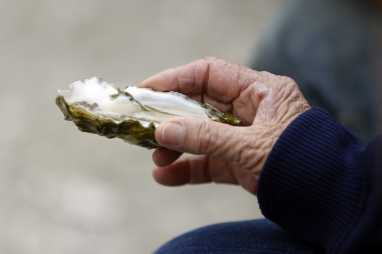 Joan Lunny, mother of Drakes Bay Oyster Company owner Kevin Lunny, holds an oyster in preparation of a toast during a celebration event at Drakes Bay Oyster Company in Inverness, California July 31, 2014. (Stephen Lam/Reuters)