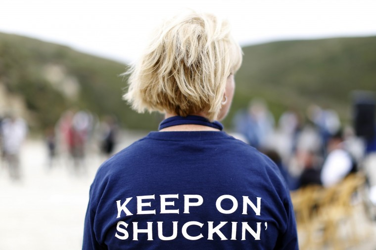 """Ginny Lunny-Cummings, farm manager at Drakes Bay Oyster Company, wears a """"keep on shucking"""" shirt during a celebration ceremony to recognize the company in Inverness, California July 31, 2014. (Stephen Lam/Reuters)"""