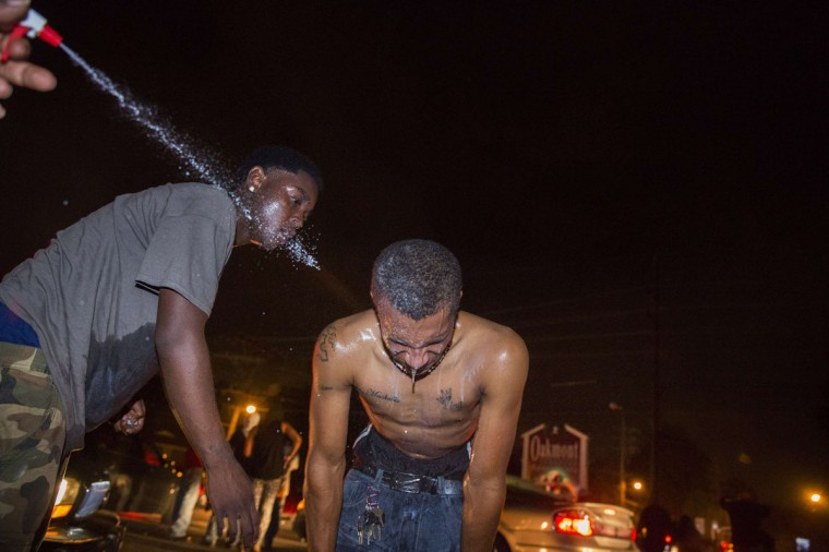 Protesters react to the effects of tear gas which was fired at demonstrators reacting to the shooting of Michael Brown in Ferguson, Missouri August 17, 2014. Shots were fired and police shouted through bullhorns for protesters to disperse, witnesses said, as chaos erupted Sunday night in Ferguson, Missouri, which has been racked by protests since the unarmed black teenager was shot by police last week. (Lucas Jackson/Reuters)