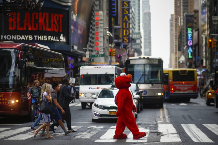 Jorge, an immigrant from Mexico, walks across an intersection dressed as the Sesame Street character Elmo, in Times Square, New York July 30, 2014. (Eduardo Munoz/Reuters)