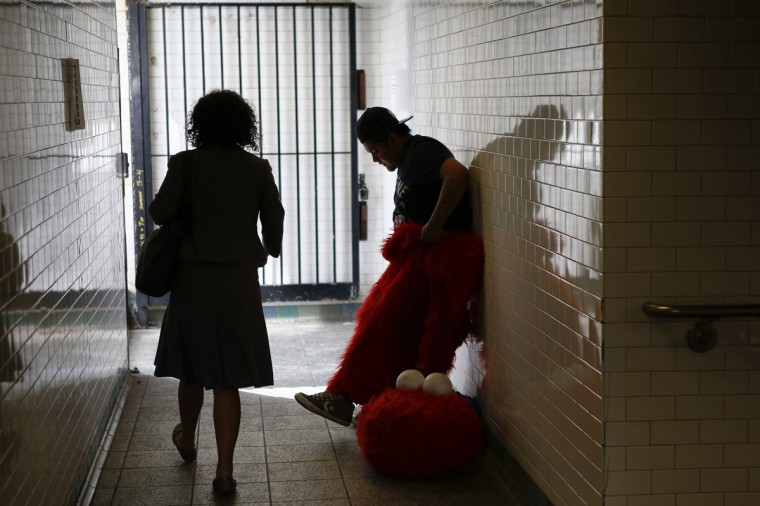 Jorge, an immigrant from Mexico, gets dressed as the Sesame Street character Elmo inside of a subway station in Times Square, New York July 30, 2014. (Eduardo Munoz/Reuters)