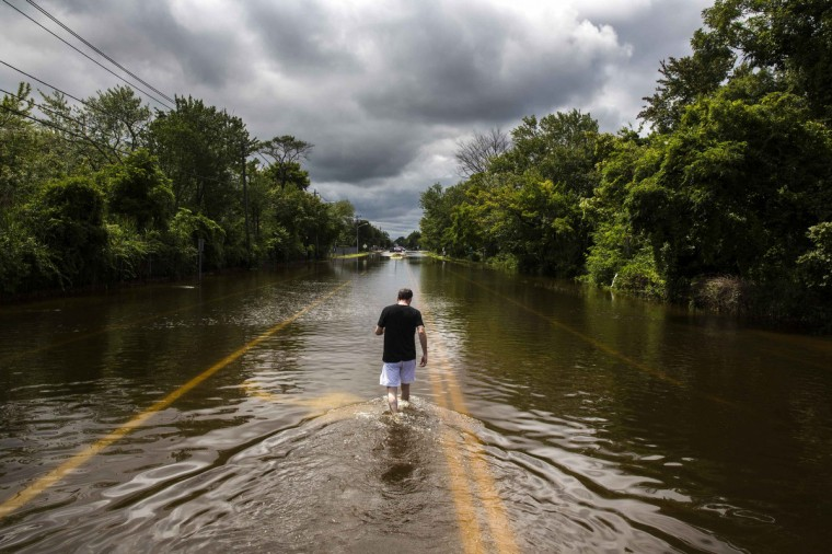 A man walks down a flooded road in Islip, New York. More than a foot of rain hit parts of New York's Long Island on Wednesday, enough to set a preliminary state record, triggering flash floods and swamping cars on major roads that were turned into rivers during the morning rush hour. (Lucas Jackson/Reuters)