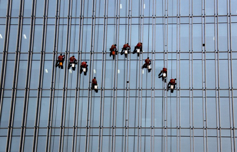 Cleaners abseil down the front of a newly constructed building in central Beijing on May 3, 2011. (REUTERS/David Gray)