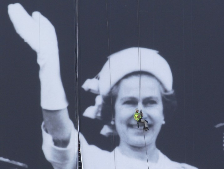 An abseiler secures a giant canvas along the River Thames of a photograph showing Britain's Queen Elizabeth and Royal Family during the 1977 Silver Jubilee, London on May 25, 2012. (REUTERS/Suzanne Plunkett)