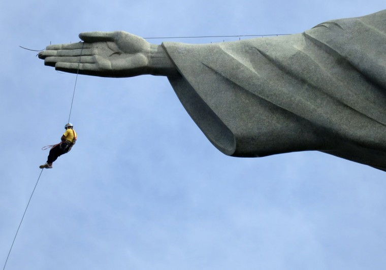 A worker rappels from the Cristo Redentor statue at the Corcovado in Rio de Janeiro on June 23, 2014. (REUTERS/Alessandro Garofalo)