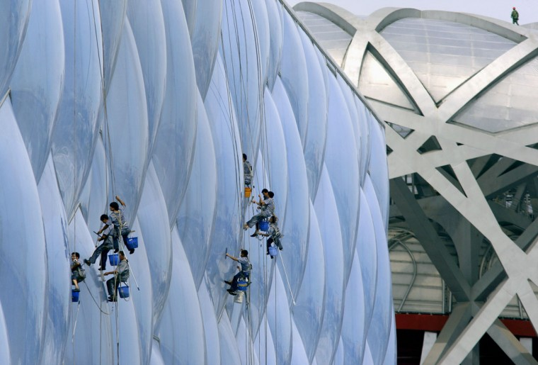 A worker walks atop the roof of the National Stadium (right), also known as the Bird's Nest, as cleaners abseil down the exterior of the National Aquatics Center, also known as the Water Cube, at the Olympic Green in Beijing on July 17, 2008. (REUTERS/David Gray)