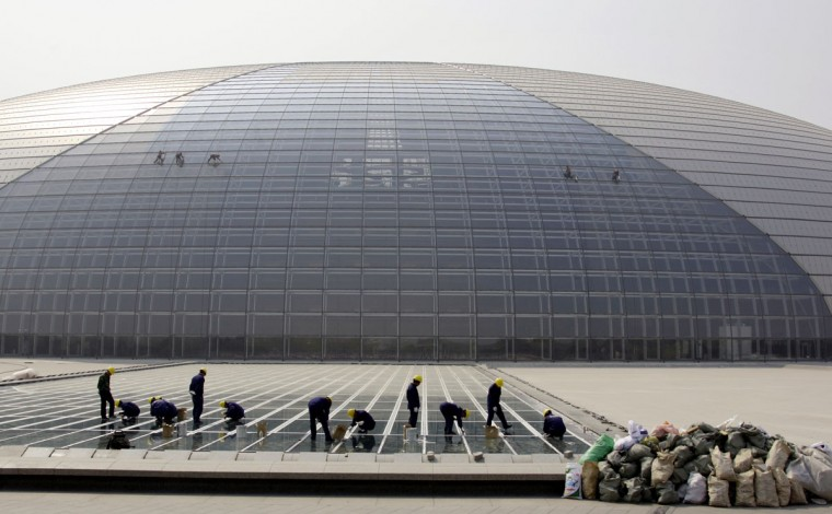 Workers clean the pool surrounding Beijing's National Grand Theatre April 9, 2009 as cleaners remove dirt while abseiling down the glass roof. The huge theatre, nicknamed 'The Egg' by locals, has three main halls consisting of a 2,416-seat opera house, a 2,017-seat concert hall with pipe organ and a 1,040-seat theatre for plays. (REUTERS/David Gray)