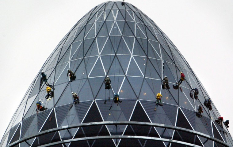 Workers abseil at the top of the Swiss Re 'gherkin' building in London in this January 14, 2004 file photo.
