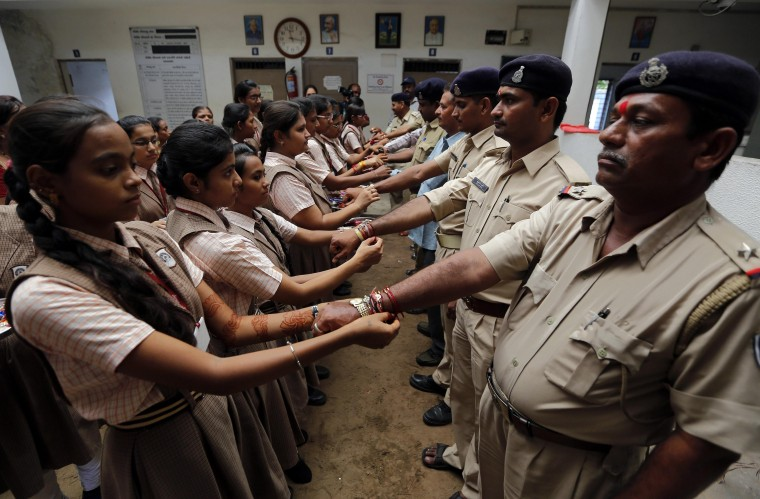 "Schoolgirls tie ""Rakhis"" or traditional Indian sacred threads onto the wrists of Indian police personnel inside a police station on the eve of Raksha Bandhan festival in the western Indian city of Ahmedabad. Rakhi is also the name of a Hindu festival, also known as Raksha Bandhan, during which a sister ties one or more of the sacred threads onto her brother's wrist to ask him for her protection. The festival will be celebrated across the country on Sunday. (Amit Dave/Reuters)"