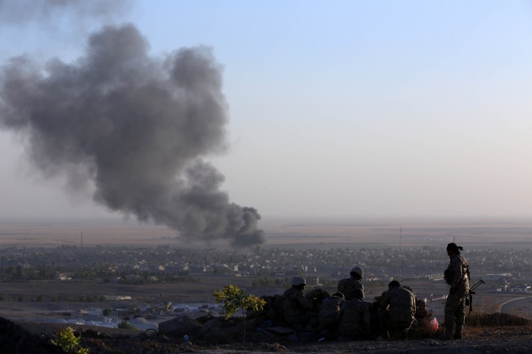 Iraqi Kurdish Peshmerga fighters look on as smoke billows from the town Makhmur, about 280 kilometres (175 miles) north of the capital Baghdad, during clashes with Islamic State (IS) militants. Makhmur, is one of the areas that had been attacked by jihadist fighters in recent days. (Safin Hamed/AFP-Getty Images)