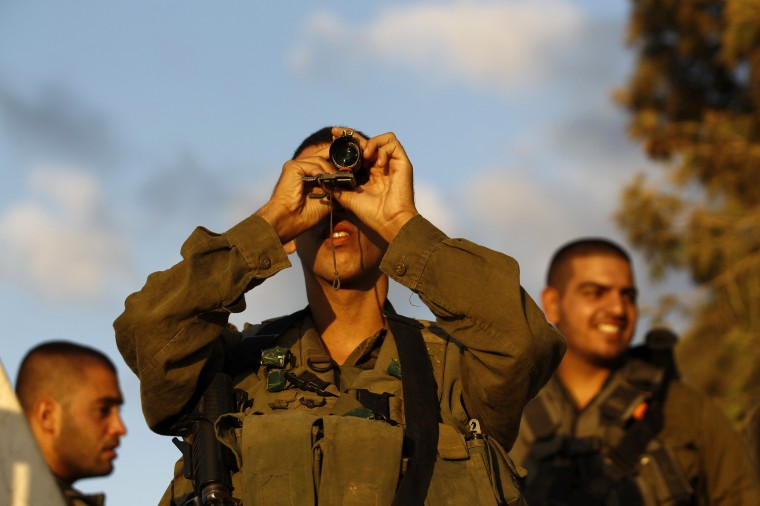 An Israeli soldier looks at the Gaza Strip through a monocular on the Israeli border. Israel launched more than 30 air attacks in Gaza on Saturday, killing five Palestinians, and militants fired rockets at Israel as the conflict entered a second month, defying international efforts to revive a ceasefire. (Amir Cohen/Reuters)