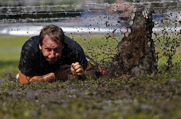 A competitor crawls through mud during the Brutal Run extreme obstacle course race in Budapest. (Laszlo Balogh/Reuters)