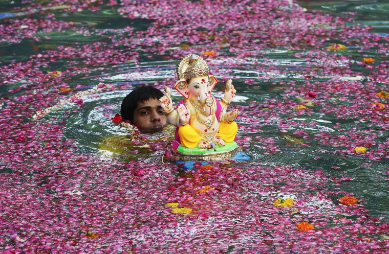 A devotee immerses an idol of the Hindu elephant god Ganesh, the deity of prosperity, in an artificial pond during the ten-day-long Ganesh Chaturthi festival in Mumbai. Ganesh idols are taken through the streets in a procession accompanied by dancing and singing, and later immersed in a river or the sea symbolising a ritual seeing-off of his journey towards his abode, taking away with him the misfortunes of all mankind. (Shailesh Andrade/Reuters)