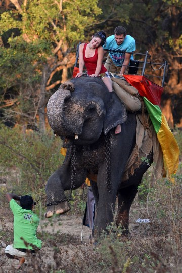 Foreign tourists pose for pictures as they ride an elephant during a sightseeing tour in the ancient city of Sigiriya, near Dambulla. The number of foreign tourists visiting Sri Lanka has swelled since the island ended a 37-year separatist conflict with Tamil Tiger rebels in May 2009. (Ishara S. Kodikara/AFP-Getty Images)